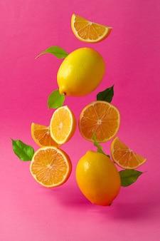 明るいピンクの背景に対して空中に浮かぶレモン