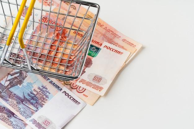 ロシアルーブルのお金でおもちゃのショッピングカート。生活賃金と購買力の概念