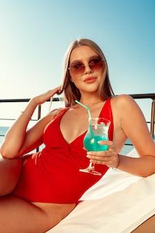 サンベッドで日光浴を完璧なボディを持つ美しい女性