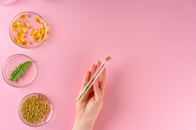 Травы и травяные пищевые добавки вид сверху на розовом фоне