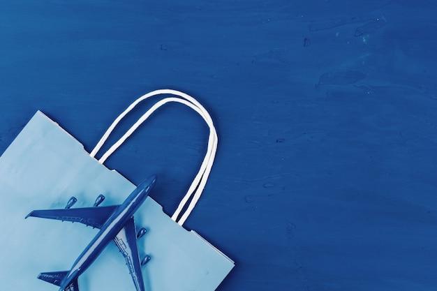 おもちゃの飛行機と古典的な青い色、トップビューでショッピングバッグ