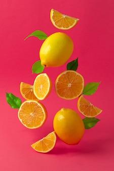 明るいピンクの部屋に対して空中を舞うレモン