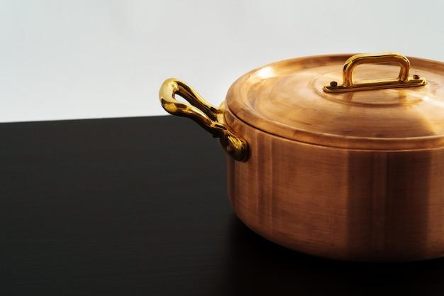 黒いテーブルの上のステンレス製の光沢のある銅鍋