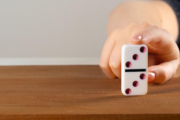 女性の手がドミノを転倒します。連鎖反応ビジネスコンセプト