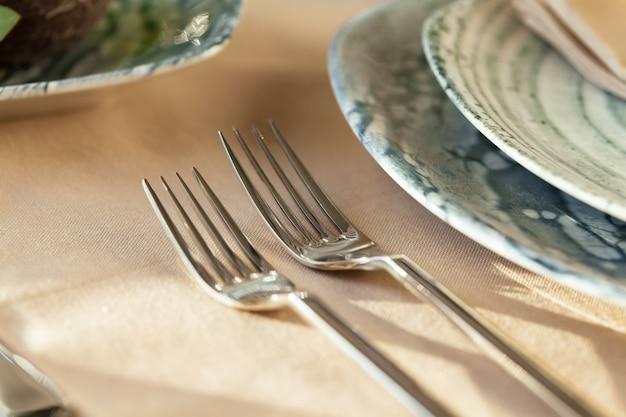 Серебряные столовые приборы на столешнице со скатертью
