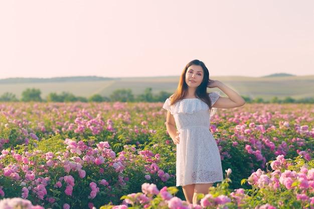Красивая молодая женщина позирует возле розы в саду.