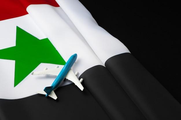 シリアの布旗の上の小さなおもちゃの飛行機
