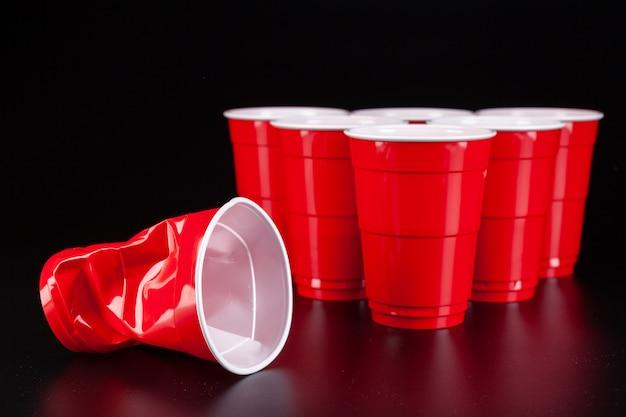 ビールピンポンのゲームのための赤いプラスチックカップとボール