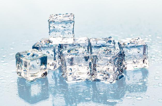 Квадратные тающие кубики льда на мокром столе