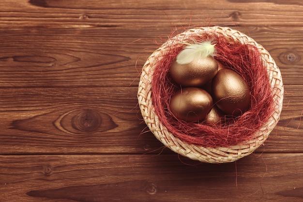 Золотые яйца на деревянный стол