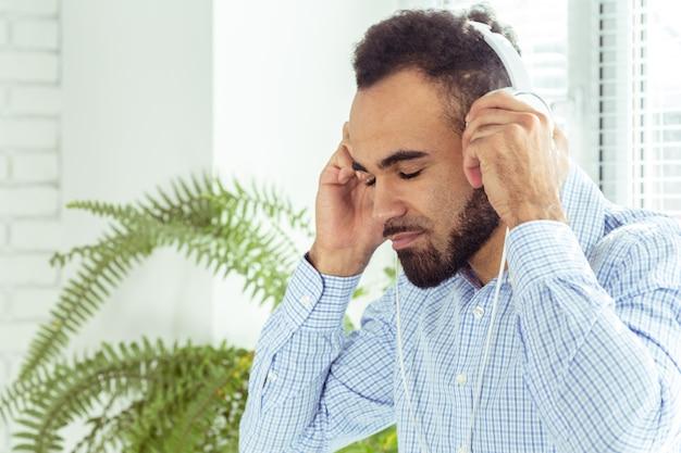Портрет афро-американского молодого человека, слушая музыку в наушниках