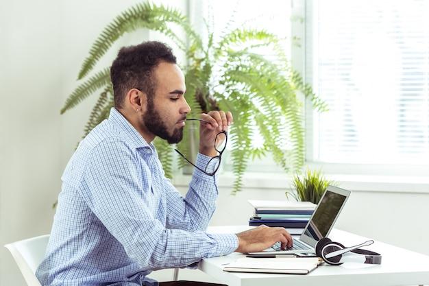 オフィスでラップトップに取り組んでいるハンサムなアフリカ黒人若いビジネスマンの肖像画