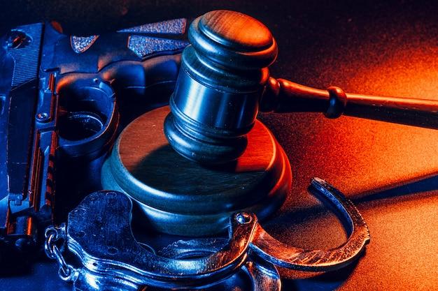 Пистолет и молоток судьи на столе. преступление, грабеж, концепция атаки