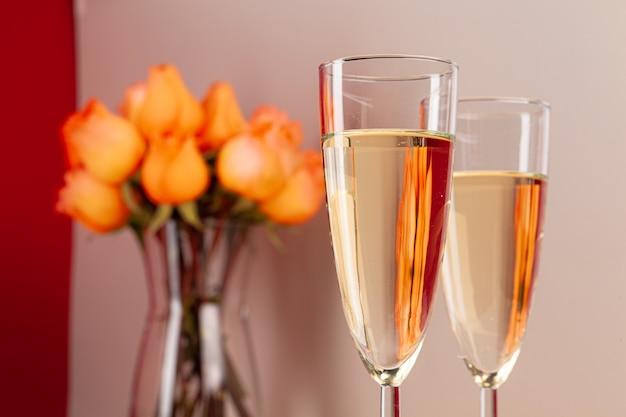 Крупным планом фото бокалов для шампанского с розами в вазе