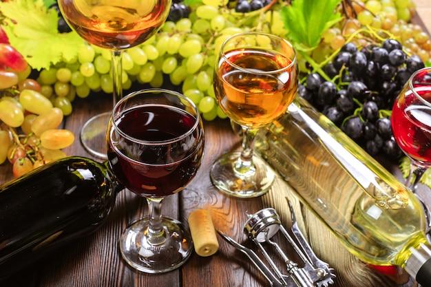 白ブドウの枝とワイン。木製のテーブルの上。
