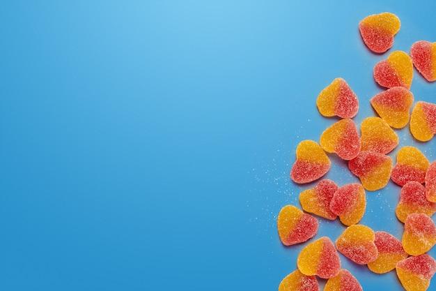 青色の背景にテーブルの上のカラフルなキャンディー