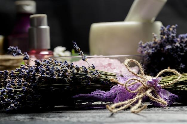Ароматическая композиция из лаванды, трав, косметики и соли на темной столешнице