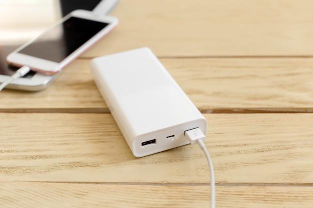パワーバンクと木製のテーブルの上の携帯電話