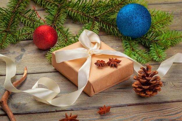 Подарочные коробки рождества и ветвь ели на деревянном столе.