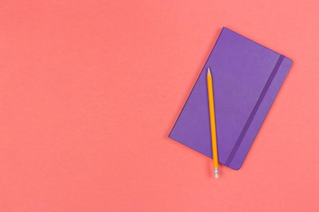 色付きの背景の上面に鉛筆で閉じたメモ帳