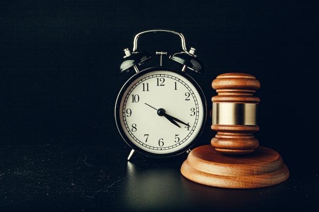 Деревянный молоток судьи с будильником на черном фоне