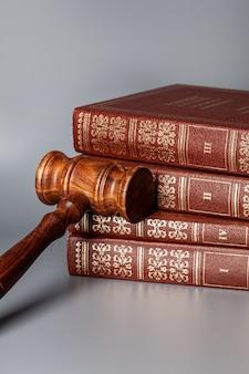 Коричневый деревянный молоток со стопкой книг на сером столе