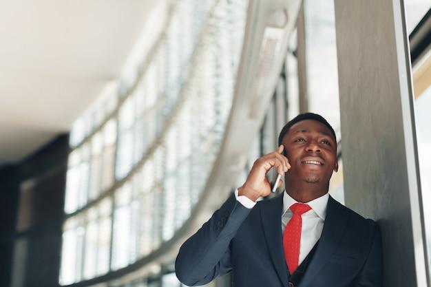 近代的なオフィスで携帯電話で話しているハンサムなアフリカ系アメリカ人実業家