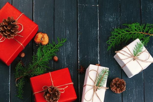 クリスマスの組成物。クリスマスプレゼント、ニット毛布、松ぼっくり、木製のテーブルにモミの枝。