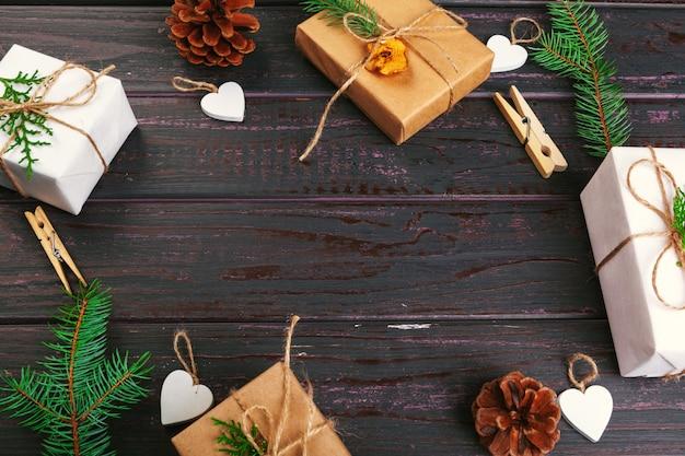 クリスマスの組成物。クリスマスプレゼント、ニット毛布、松ぼっくり、木製のテーブル背景にモミの枝。