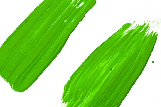 白い紙の上のペイントブラシの緑のストローク