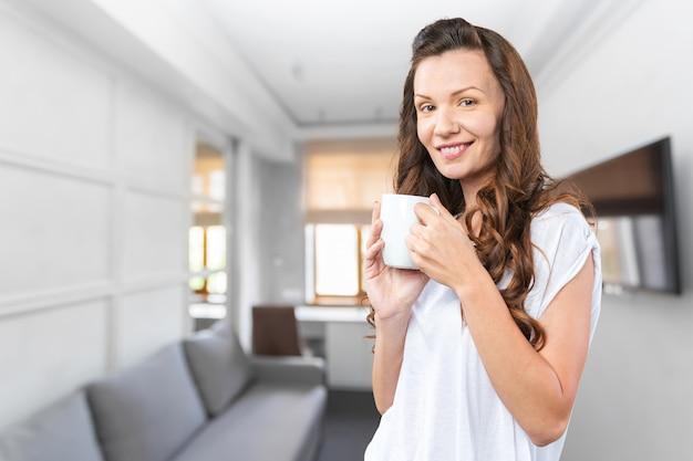 お茶のカップを持つ美しい女性