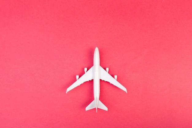 モデル飛行機、パステルカラーの背景上の飛行機。フラットレイアウトデザイン。