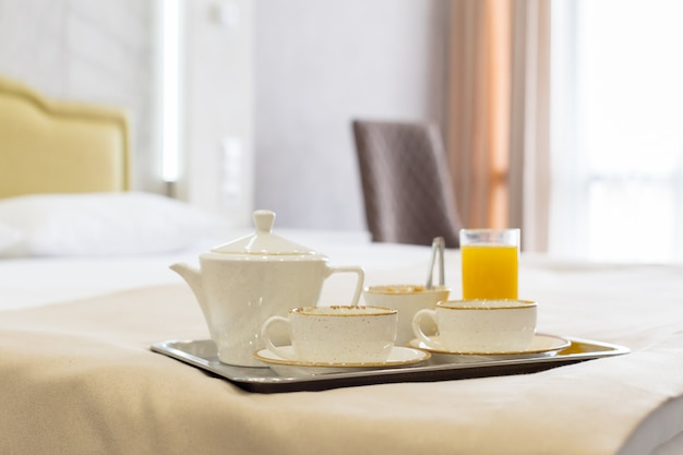 Две белые кружки на подносе белая кровать, концепция завтрака
