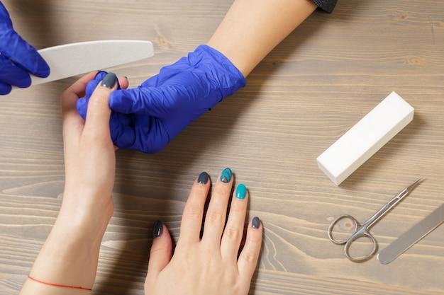 Руки женщины получают маникюр в салоне красоты
