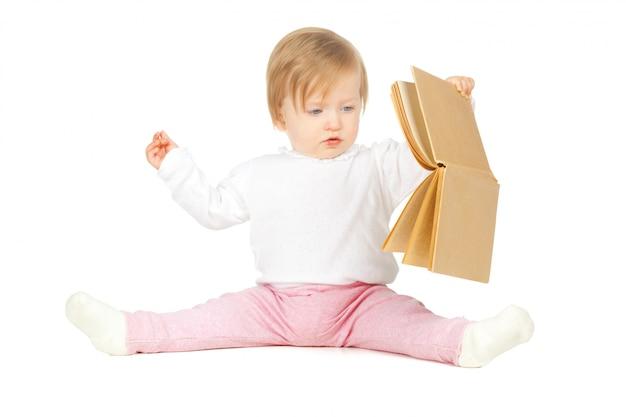 白い背景で隔離の本を保持している白人の赤ちゃん女の子