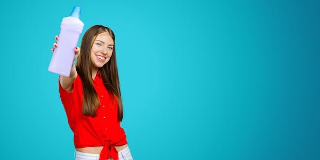 液体洗剤のボトルを保持しているカジュアルな若い女性