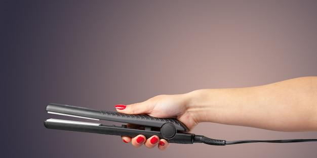 Женская рука с утюжком для волос на цветном фоне