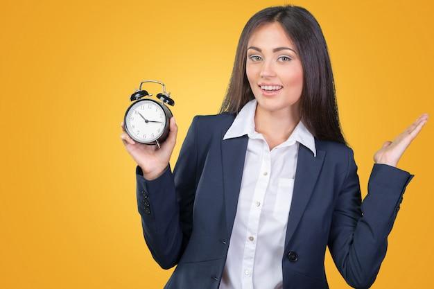 Молодая женщина, держащая часы. концепция управления временем.