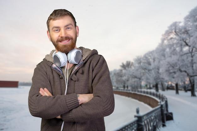 Счастливый молодой человек слушает музыку в наушниках