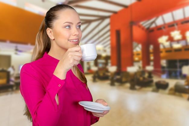 一杯のコーヒーで美しく、笑顔の女性