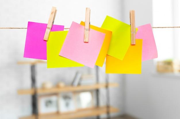 ロープに固定されているコピースペースで空白の紙のノート