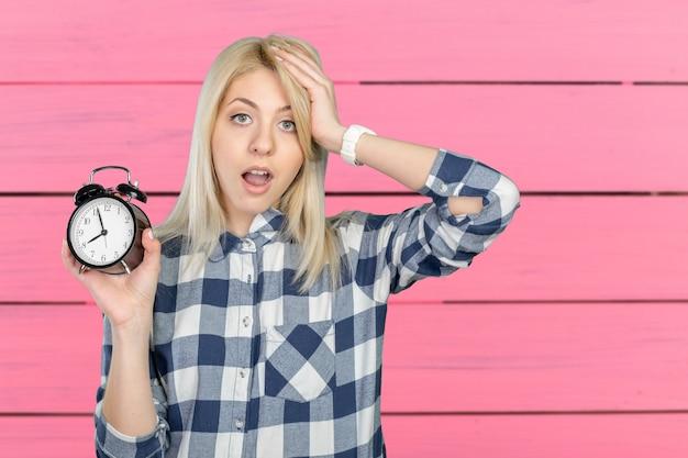 Обеспокоенная молодая женщина указывая на часы