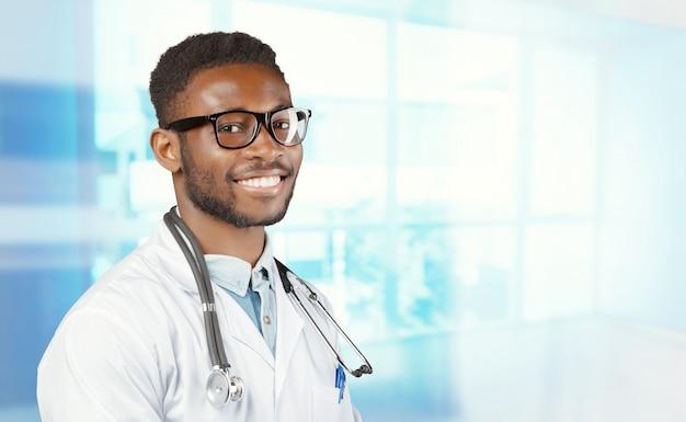 Афро-американский врач с стетоскоп, стоя на размытом фоне