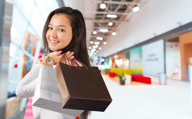 買い物袋を持つ白人の幸せな若い女性