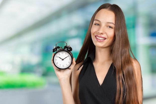 Молодая женщина держит часы