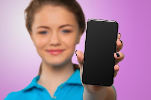 Улыбается молодая женщина, показывая пустой смартфон