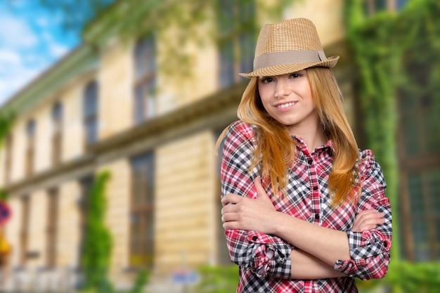 Стройная милая молодая женщина в соломенной шляпе