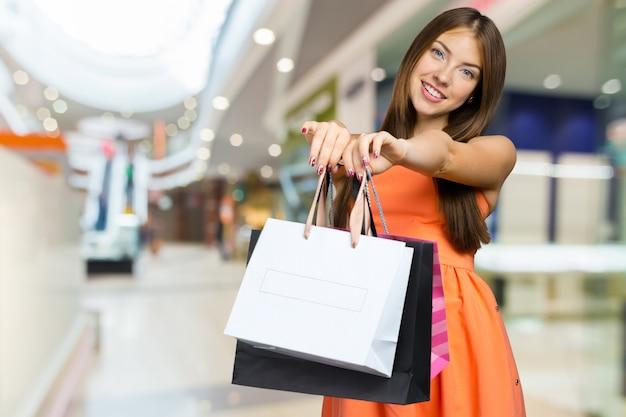 買い物袋を持つ女性の笑みを浮かべてください。