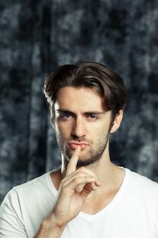 Молодой человек с пальцем на губах просит тишины