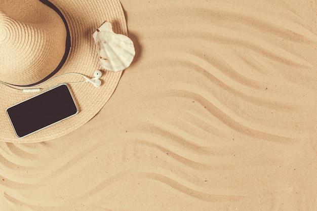 スマートフォンと貝殻で熱帯の砂浜に置かれた夏の帽子